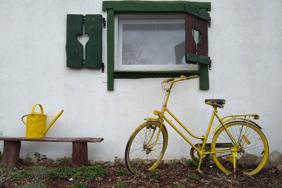 Yellow watering can and bike